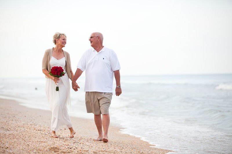 Vow Renewal - Older couple walking on beech